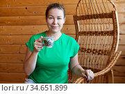 Portrait of an adult woman wearing green t-shirt holding a cup of coffee, one person sitting rattan chair at home. Стоковое фото, фотограф Кекяляйнен Андрей / Фотобанк Лори