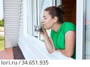 Woman drinking tea or coffee while staying in window frame of her country house, side view. Стоковое фото, фотограф Кекяляйнен Андрей / Фотобанк Лори