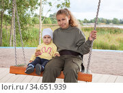 Two Caucasian girls of one year and twenty years old sitting together on swing, sisters play on playground. Стоковое фото, фотограф Кекяляйнен Андрей / Фотобанк Лори