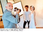 Erfahrener Hochzeitsfotograf macht Fotos vom Brautpaar am Hochzeitstag. Стоковое фото, фотограф Zoonar.com/Robert Kneschke / age Fotostock / Фотобанк Лори