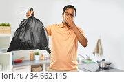 indian man holding stinky trash bag. Стоковое фото, фотограф Syda Productions / Фотобанк Лори