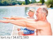 Zwei Senioren Männer strecken die Arme bei der Rückengymnastik am... Стоковое фото, фотограф Zoonar.com/Robert Kneschke / age Fotostock / Фотобанк Лори
