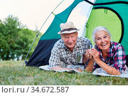 Lachendes Paar Senioren im Zelt mit einem Becher Kaffee im Camping... Стоковое фото, фотограф Zoonar.com/Robert Kneschke / age Fotostock / Фотобанк Лори
