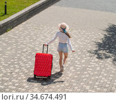 Caucasian woman walking down the street with a red suitcase. Стоковое фото, фотограф Михаил Решетников / Фотобанк Лори