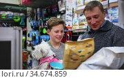 Father and son during selecting dry food in petshop. Стоковое видео, видеограф Яков Филимонов / Фотобанк Лори