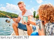 Junge und Vater beim Angeln am See am Wochenende mit einem Becher... Стоковое фото, фотограф Zoonar.com/Robert Kneschke / age Fotostock / Фотобанк Лори