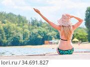 Junge Frau im Bikini in der Sonne am Badesee oder Meer freut sich... Стоковое фото, фотограф Zoonar.com/Robert Kneschke / age Fotostock / Фотобанк Лори