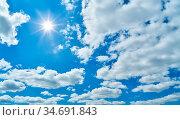 Blauer Himmel mit einer strahlenden Sonne und weißen Wolken. Стоковое фото, фотограф Zoonar.com/Robert Kneschke / age Fotostock / Фотобанк Лори