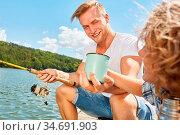 Junge gibt seinem Vater einen Becher Kaffee beim Angeln am See am... Стоковое фото, фотограф Zoonar.com/Robert Kneschke / age Fotostock / Фотобанк Лори
