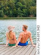 Junges Paar sitzt auf einem Holzsteg an einem Badesee im Urlaub im... Стоковое фото, фотограф Zoonar.com/Robert Kneschke / age Fotostock / Фотобанк Лори