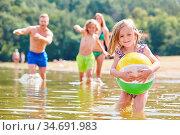 Kleines Mädchen mit einem Ball spielt mit ihrer Familie zusammen ... Стоковое фото, фотограф Zoonar.com/Robert Kneschke / age Fotostock / Фотобанк Лори