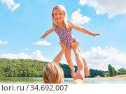 Glückliches kleines Mädchen beim Fliegen spielen in den Hände des... Стоковое фото, фотограф Zoonar.com/Robert Kneschke / age Fotostock / Фотобанк Лори