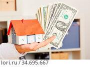 Weibliche Hand hält Dollar und ein kleines Haus als Symbol für Baufinanzierung. Стоковое фото, фотограф Zoonar.com/Robert Kneschke / age Fotostock / Фотобанк Лори