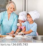 Zwei Enkel helfen der Oma beim Backen von Keksen zu Weihnachten in... Стоковое фото, фотограф Zoonar.com/Robert Kneschke / age Fotostock / Фотобанк Лори