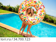 Girls stand holding inflatable doughnut near pool. Стоковое фото, фотограф Сергей Новиков / Фотобанк Лори