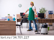 Young male contractor cleaning the office. Стоковое фото, фотограф Elnur / Фотобанк Лори