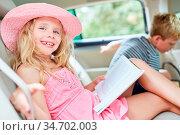 Glückliches Mädchen mit einem Buch auf der Reise auf der Rückbank... Стоковое фото, фотограф Zoonar.com/Robert Kneschke / age Fotostock / Фотобанк Лори