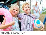 Lachendes Geschwister Paar mit Ball und Schwimmring freut sich auf... Стоковое фото, фотограф Zoonar.com/Robert Kneschke / age Fotostock / Фотобанк Лори