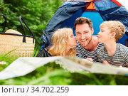 Geschwister Kinder geben ihrem Vater einen Kuss beim Camping im Sommer... Стоковое фото, фотограф Zoonar.com/Robert Kneschke / age Fotostock / Фотобанк Лори