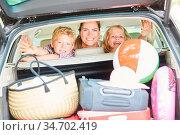 Mutter und Kinder im Auto mit viel Gepäck im Kofferraum vor der Reise. Стоковое фото, фотограф Zoonar.com/Robert Kneschke / age Fotostock / Фотобанк Лори