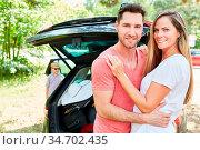 Glückliches Eltern Paar steht vor dem Auto und freut sich auf den... Стоковое фото, фотограф Zoonar.com/Robert Kneschke / age Fotostock / Фотобанк Лори