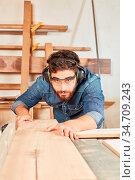 Schreiner mit Gehörschutz arbeitet konzentriert mit Holz an der Säge... Стоковое фото, фотограф Zoonar.com/Robert Kneschke / age Fotostock / Фотобанк Лори