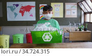 Boy wearing face mask holding recycle container in class at school . Стоковое видео, агентство Wavebreak Media / Фотобанк Лори