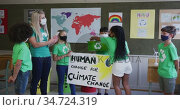 Group of kids holding climate change banner and recycle container at school. Стоковое видео, агентство Wavebreak Media / Фотобанк Лори
