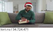 Man wearing Santa hat opening gift box while having video chat on his laptop. Стоковое видео, агентство Wavebreak Media / Фотобанк Лори