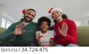 Family smiling and waving at the camera while siting on the couch. Стоковое видео, агентство Wavebreak Media / Фотобанк Лори