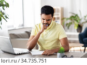 indian man with notebook and laptop at home office. Стоковое фото, фотограф Syda Productions / Фотобанк Лори
