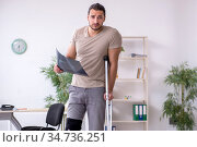 Young leg injured man with crutches looking x-ray. Стоковое фото, фотограф Elnur / Фотобанк Лори