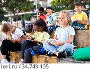 Preteen classmates preparing schoolwork outside school. Стоковое фото, фотограф Яков Филимонов / Фотобанк Лори