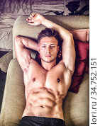 Shirtless sexy young man in panties relaxing on sofa and looking at... Стоковое фото, фотограф Zoonar.com/STEFANO CAVORETTO / easy Fotostock / Фотобанк Лори