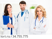 Successful team of medical doctors are looking at camera and smiling... Стоковое фото, фотограф Zoonar.com/Ivan Mikhaylov / easy Fotostock / Фотобанк Лори