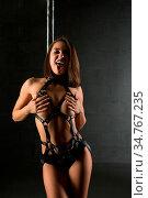 Pretty girl wearing bdsm style belts against pylon cropped shot. Стоковое фото, фотограф Zoonar.com/Andrey Guryanov / easy Fotostock / Фотобанк Лори