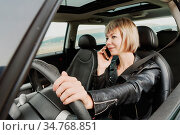 Business girl in leather jacket at the wheel of a car is wearing a... Стоковое фото, фотограф Zoonar.com/Ian Iankovskii / easy Fotostock / Фотобанк Лори