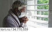 Senior man wearing face mask looking out of window at home. Стоковое видео, агентство Wavebreak Media / Фотобанк Лори