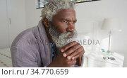 Senior man holding his walking stick while sitting on bed at home. Стоковое видео, агентство Wavebreak Media / Фотобанк Лори