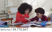 Mother helping son with homework at home. Стоковое видео, агентство Wavebreak Media / Фотобанк Лори
