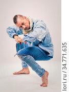 Caucasian male dancer wearing blue denim shirt and pants on light... Стоковое фото, фотограф Zoonar.com/Zdenka Darula / easy Fotostock / Фотобанк Лори