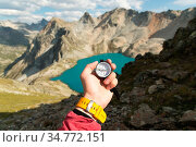 A man's hand holds a pocket magnetic compass for navigation against... Стоковое фото, фотограф Zoonar.com/Ian Iankovskii / easy Fotostock / Фотобанк Лори