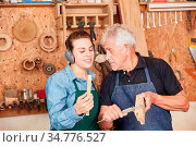 Handwerker Lehrling und Schreiner Meister messen Holz mit dem Messschieber. Стоковое фото, фотограф Zoonar.com/Robert Kneschke / age Fotostock / Фотобанк Лори