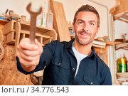 Junger Mann als Handwerker mit Schraubenschlüssel in seiner Tischler... Стоковое фото, фотограф Zoonar.com/Robert Kneschke / age Fotostock / Фотобанк Лори