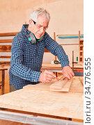 Senior Mann als Schreiner mit Bleistift beim Abmessen von Holz in... Стоковое фото, фотограф Zoonar.com/Robert Kneschke / age Fotostock / Фотобанк Лори