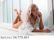 Gorgeous blonde with long locks in underwear lying on her stomach... Стоковое фото, фотограф Zoonar.com/Andrey Guryanov / easy Fotostock / Фотобанк Лори