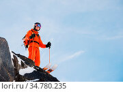 Professional skier-athlete stands on the edge of a high rock against... Стоковое фото, фотограф Zoonar.com/Ian Iankovskii / easy Fotostock / Фотобанк Лори