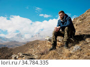 A portrait of a stylish bearded hipster sitting on a rock against... Стоковое фото, фотограф Zoonar.com/Ian Iankovskii / easy Fotostock / Фотобанк Лори