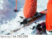 Orange alpine ski boots in a ski mount. One boot is completely fixed... Стоковое фото, фотограф Zoonar.com/Ian Iankovskii / easy Fotostock / Фотобанк Лори