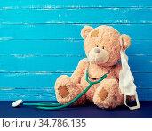 Big teddy bear is sitting in a white medical mask, green stethoscope... Стоковое фото, фотограф Zoonar.com/Danko Natalya / easy Fotostock / Фотобанк Лори